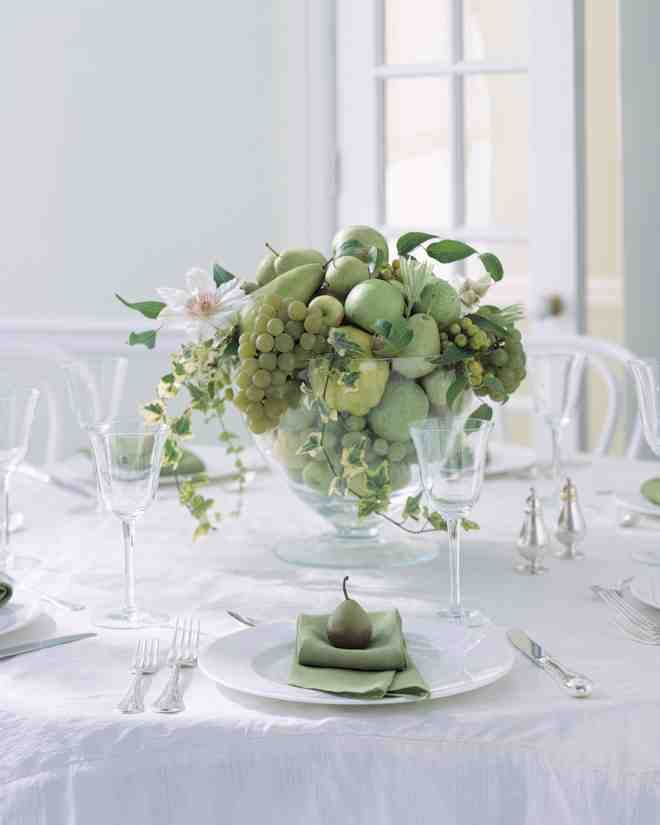 A clear glass footed bowl stocked plentifully with fresh green fruit—quince, grapes, Anjou pears, apples, and chinaberries—makes a striking focal point on a round table. Variegated ivy and white blooming clematis vines add a graceful accent.