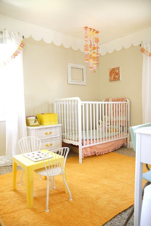 We spot a trend: saffron!  Whimsical nursery space with vintage accents in pastels and a bright yellow rug