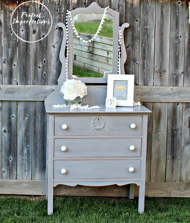 grey whitewashed dresser with simple porcelain knobs and sweet wreath applique