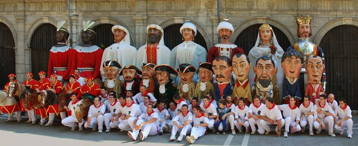 Pamplona's Giants and Big-heads parade family photo. From back to front and left to right we can see the American, Asian, African and European pairs of giants (last row), the six kilikis and the 5 big-heads (second row), the zaldikos, and members of the parade who carry the figures (front row).