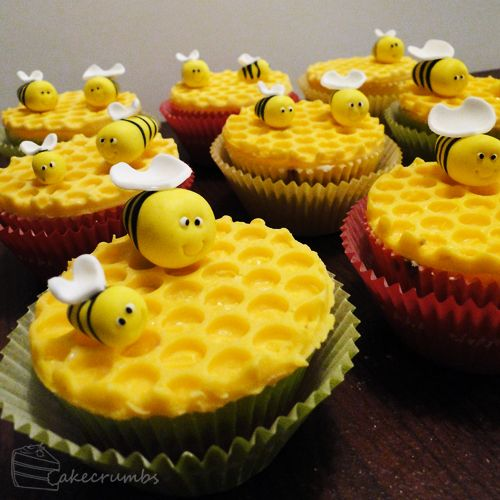 Plain cupcakes are covered in yellow fondant which has been cut to look like honeycomb and then very cute little fondant bees are placed on the top.