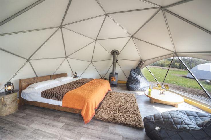 Un intérieur en forme de dôme avec lit, fauteuil poire et poêle à bois