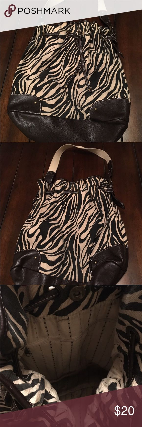 Banana Republic Zebra Bucket Tote Banana Republic bucket tote. Zebra print canvas with dark leather bottom. Adjustable canvas and leather strap. Inside is lined and has one zipper pocket. Leather drawstring and magnetic snap closure. This bag holds everything and looks cute doing it. Clean with no tears or stains or smells. Banana Republic Bags Shoulder Bags