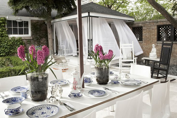 Chic patio features covered pergola dressed in white sheer curtains situated next to zen garden ...
