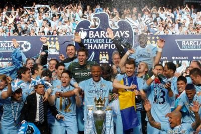 The Manchester City team celebrate winning the English Premier League following their match against Queens Park Rangers at the Etihad Stadium in Manchester, northern England. REUTERS/Darren Staples