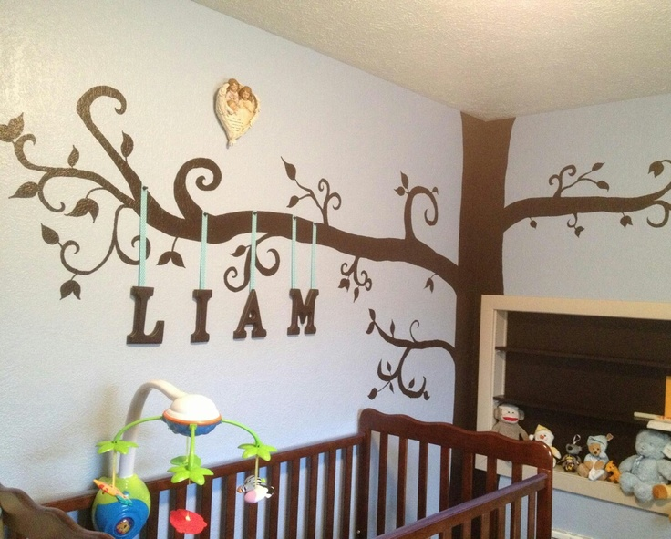 """Whimsical tree painted in corner with wooden letters hanging from ribbons on """"branches"""". Very cute!"""
