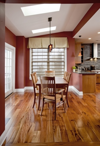 "The informal dining area was enlarged to give our clients a functional eating area.The space was enlarged by an 18"" exterior wall bump out which incorporates an 8 foot sliding French door that provides easy access to the new rear deck. Sage glass skylights by Velux change color on demand to diminish strong, unwanted sunlight. Unique decorative lighting was chosen to give the space a modern twist."