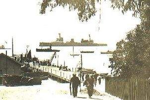 Looking down Wharf Street circa 1913, to the Fish Market and the Town Jetty. HMS New Zealand lies in the background. Simonstown