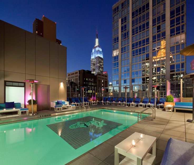 Rooftop pool at the Gansevoort Hotel Park Avenue, New York City, New York, USA. It's located at 420 Park Ave. S. in Midtown Manhattan. In the centre background is the Empire State Building at 350 5th Ave. The Empire State Building gets lit up different colours for special occasions…
