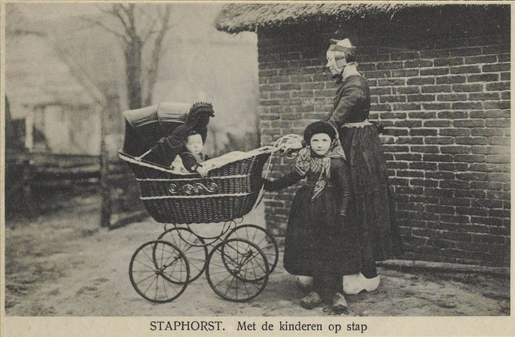 Vrouw met meisje en jongetje in Staphorster streekdracht, met kinderwagen