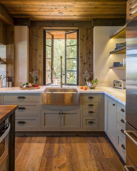 Rustic kitchen with cabinets painted in Benjamin Moore Gettysburg Grey, hardwood floors, black framed windows, and a stainless steel farmhouse sink | HomeBunch