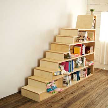 Bookshelves in the shape of a staircase, with a seat at the top. Created