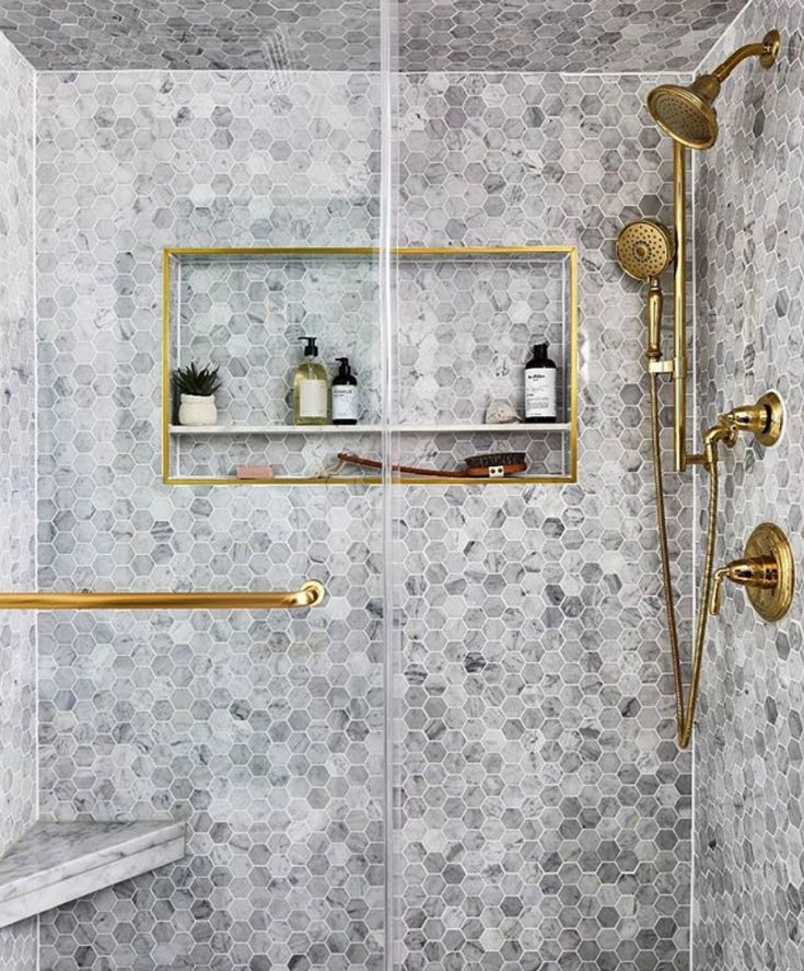 Small grey hexagonal tiles used in a shower setting with shiny gold features on the shower.