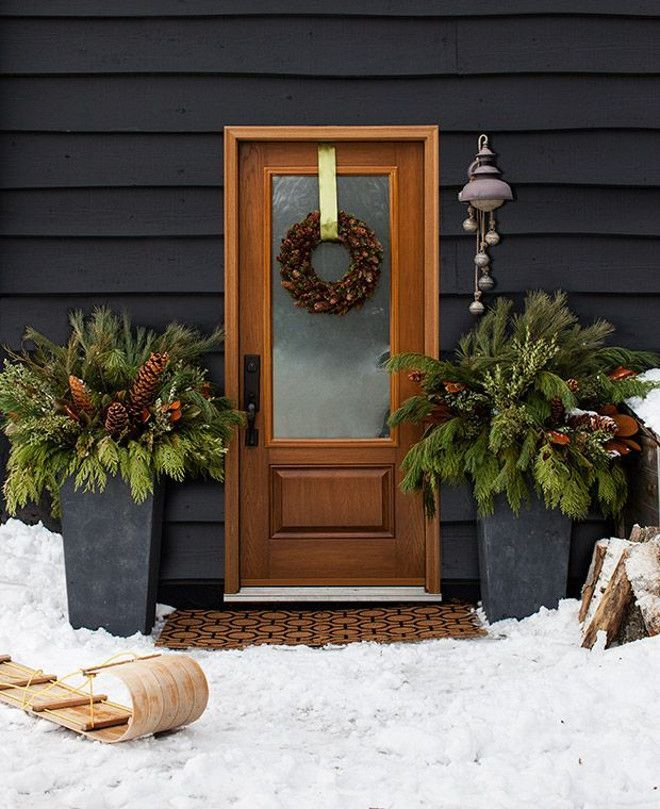 Simple home entrance with black siding, a rustic front door, potted pine and a holiday wreath | House & Home.