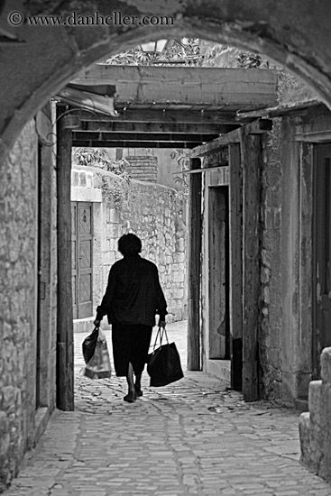woman-carrying-bags-bw.jpg bags, black and white, carrying, croatia, europe, images, narrow streets, streets, trogir, vertical, womens