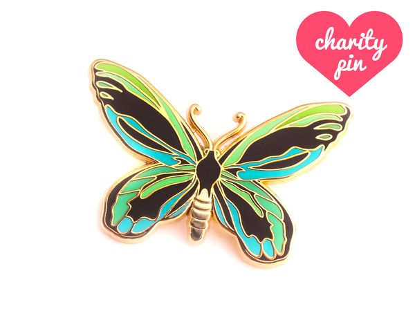 "Queen Alexandra's birdwing butterfly, native to the Oro province in eastern Papua New Guinea, is the largest butterfly in the world! It is critically endangered, threatened by both habitat destruction and illegal poaching.  THE NITTY GRITTY ✎ Designed in collaboration with Natelle Draws Stuff✎ One 1.5-inch (38mm) hard enamel pin, made from an original illustration by Oh Plesiosaur and Natelle Draws Stuff ✎ Shiny gold metal✎ Two rubber pin backs ✎ ""OH PLESIOSAUR"" and ""NATEL..."