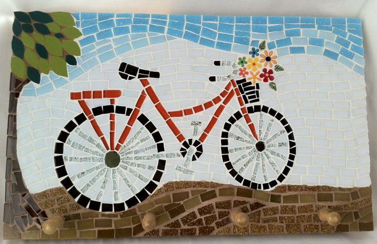 Um símbolo de liberdade e prazer, a bicicleta que decora esse cabideiro foi trabalhada em pastilhas de vidro, azulejos especiais, flores em cerâmica e pastilhas cristal. <br>O cabideiro possui 4 pinos de madeira, super reforçados, que podem ser usados para acomodar toalhas, roupões, guarda-chuvas, aventais, guardanapos,capas de chuvas ou quaisquer outros objetos que estejam precisando de um local bonito e criativo para serem organizados! <br> <br>Tamanho: 26 cm de largura x 43 cm de…
