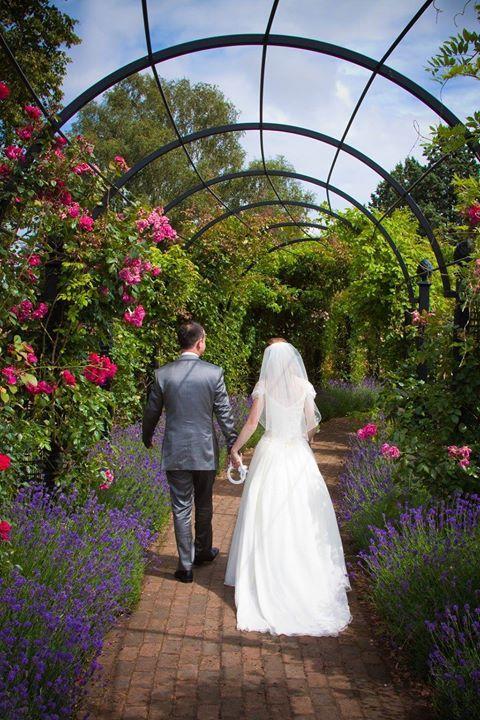 Das beliebte Foto-Motiv für frisch Gertrauten: gemeinsam spazieren gehen durch den Rosen-Laubengang von Classic Garden Elements im Royal National Rose Society - Garden of the Rose in St Albans.