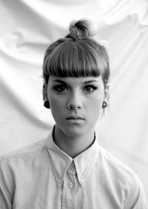 Black & White Photo of Girl Wearing Nose Hoop, Ear Tunnels, & A High Hair Bun