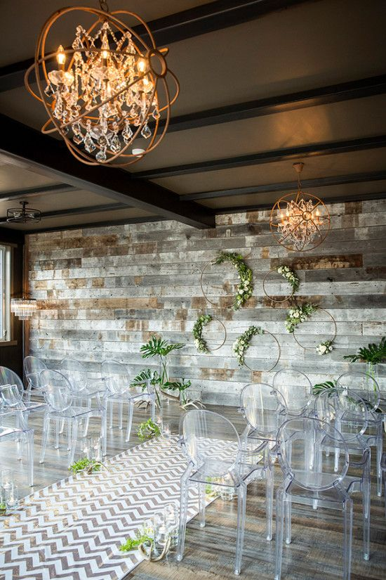 Love this modern rustic wedding reception decor that uses reclaimed wood for a wall.
