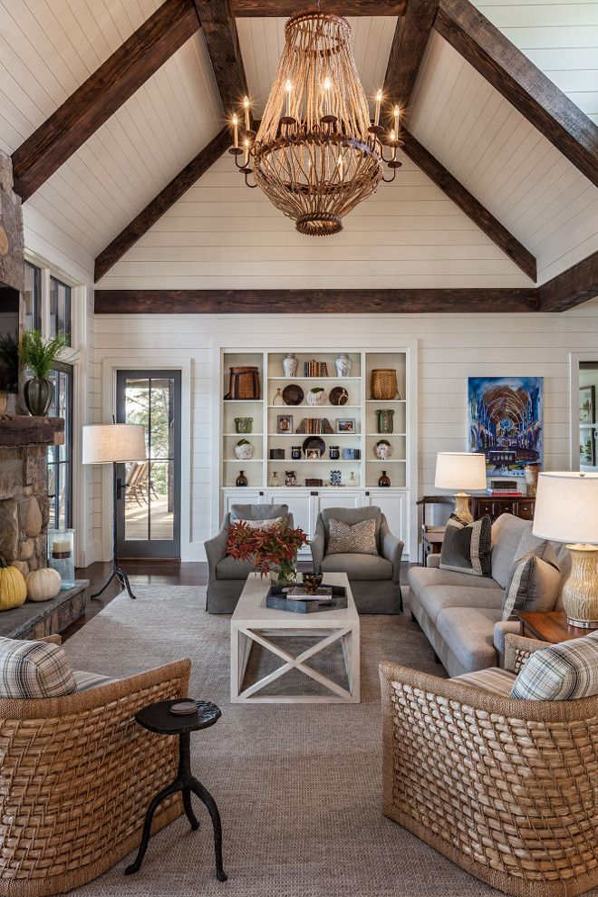 Farmhouse Living room with floor to ceiling shiplap. Farmhouse Living room features floor-to-ceiling shiplap, exposed beams on vaulted ceilings, rope and iron chandelier and a pair of natural fiber chairs. Chandelier is a Luigi Chandelier by Solaria Lighting.