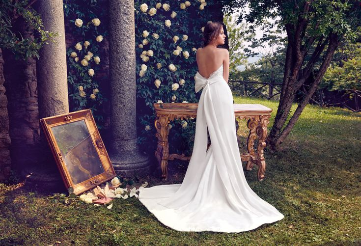 Slim strapless wedding dress in silk with plunging back and a large loop of Giuseppe Papini