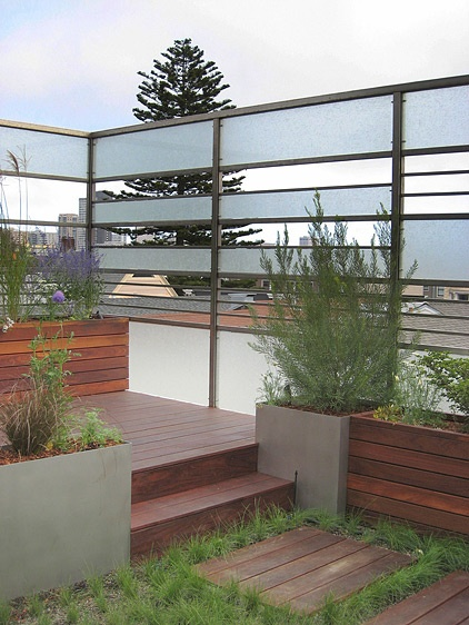 Roof deck & garden with a metal & glass fence.  Love the multi-levels!  the wall is on the honeydo list