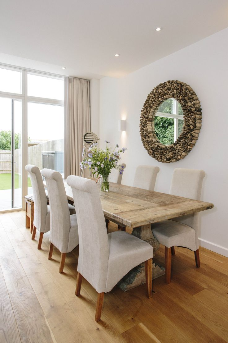 The large dining table at 1 The Sands, a self-catering holiday cottage in Polzeath, North Cornwall. The open plan living space provides the ideal spot for entertaining.