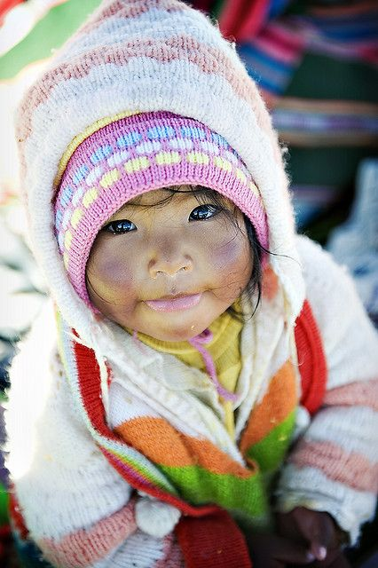 Straw Child - This adorable child was one of the children living on a floating island of straw on Lake Titicaca, Peru. The entire island, including the houses and boats are made of straw | Priscilla Locke #world #cultures