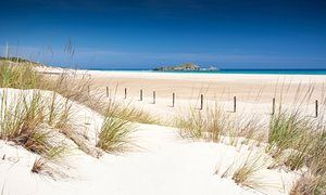 The wide soft sands of huge Su Giudeu beach in the south of Sardinia is on a spit between lagoon and sea.