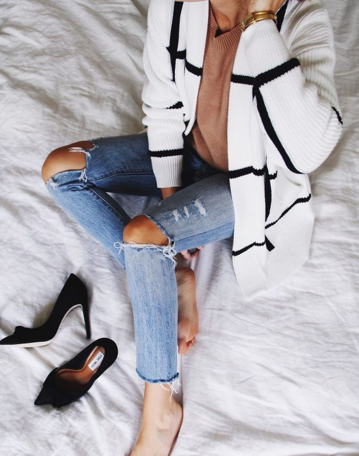 white and black cardigan with camel sweater and ripped levi's