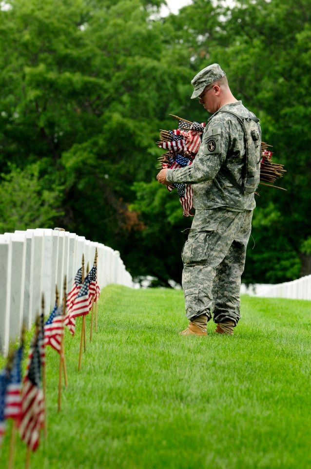 A 3d U.S. Infantry Regiment (The Old Guard) Soldier places an American flag in front of fallen veteran's grave stone at Arlington National Cemetery. Each year for the past 40 years, the 3d U.S. Infantry Regiment has honored America's fallen heroes by placing American flags at gravestones just prior to Memorial Day weekend. (Photo by Sgt. Jose Torres)