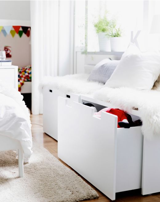 Close-up of IKEA STUVA storage benches with sheepskins and cushions on top.