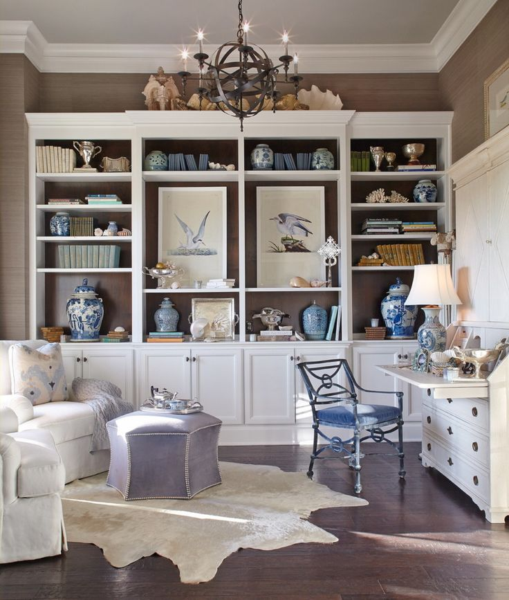 Home office with custom cabinets and shelving, cowhide rug, chandelier, pull out desk |  CDA Interior Design
