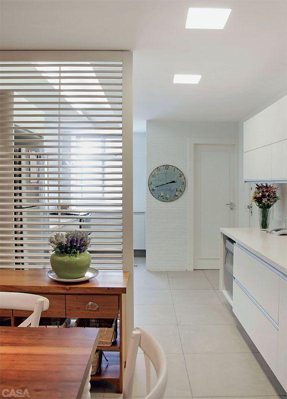 Uma divisória leve – o painel de venezianas articuladas (Marcenaria Cristal da Serra) – separa a cozinha da copa. Abertas, as lâminas deixam vazar a luz da janela da lavanderia. Fechadas, tornam a área de refeições mais privativa.