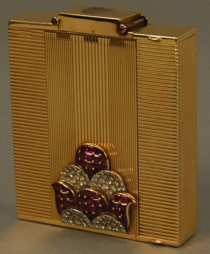Ostertag Art Deco 18K yellow gold compact having compartments for lipstick, lighter, mirror, powder, watch, and comb, set with 66 rubies and 66 diamonds, each piece having an eagle head touch mark, marked Ostertag Paris Depose 39149, 289.9 grams - Realized Price: $19,200.00
