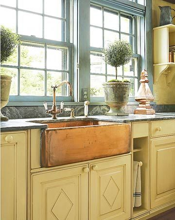 Farmhouse Sink Patina  A copper apron-front sink adds a warm patina to this rustic cottage kitchen. Green marble countertops keep the design simple but elegant.