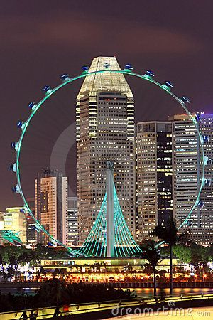 Singapore flyer with skyscrapers on background at night, view from Marina Barrage