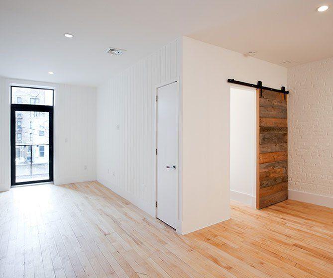 reclaimed maple factory floors with oak sliding barn door, black door frames