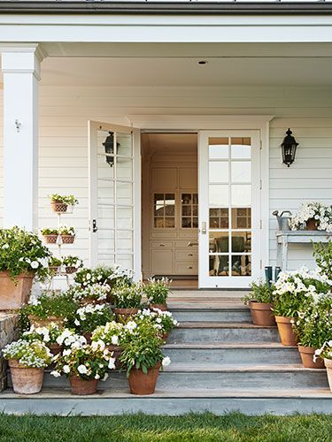 White flowers—including salvia, violas, petunias, begonias, and lantana—adorn the charming side porch of this California farmhouse. LOVE!