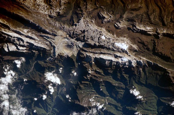 Earth Shot of the Grasberg Mine. Located in the Sudirman Mountains of the Irian Jaya province of Indonesia, the Grasberg complex (also known as the Freeport Mine) is one of the largest gold & copper mining operations in the world. The Sudirman Mountains form the western portion of the Maoke Range that extends across Irian Jaya from the west to the east-southeast. These ranges were formed by ongoing collision of the northward-moving Australian & westward-moving Pacific tectonic plates.....