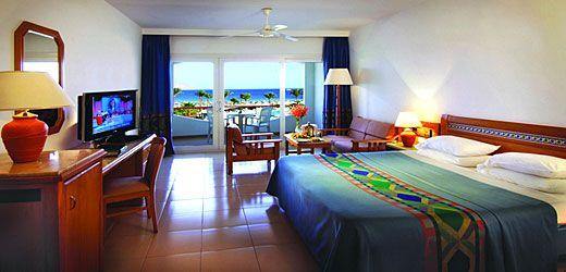 Baron Resort ~ Amiso Travel Dobbeltværelser til to eller tre personer eller til to voksne med to børn under seks år.Alle værelser har eget badeværelse og balkon.Alle værelser har også airconditioning, et lille køleskab, tv og hårtørrer.
