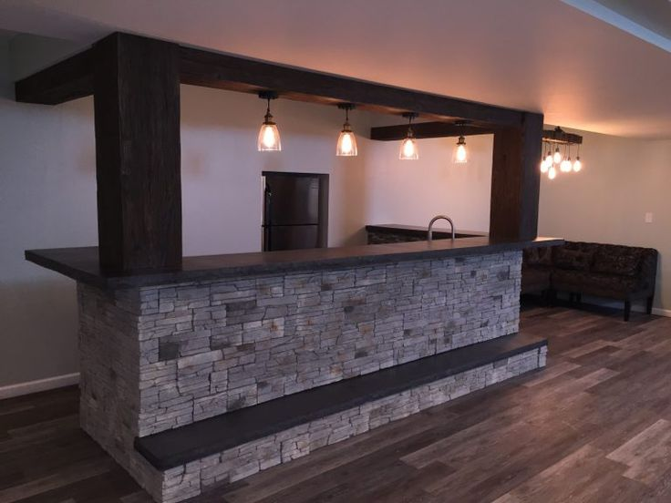 Stunning Home Basement Bar Design Incorporating Faux Beams And Stone Veneer.