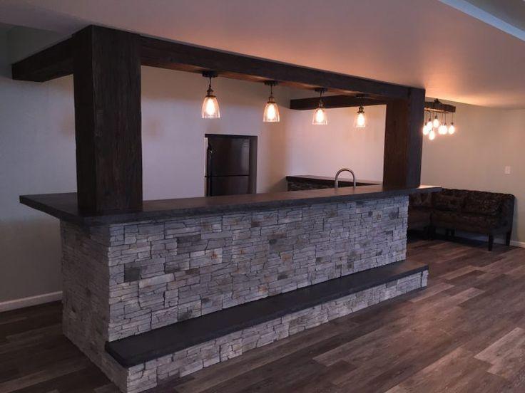 Stunning home basement bar design incorporating faux beams and stone veneer.