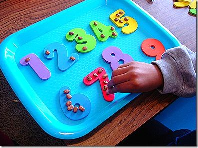 Foam numbers (dollar store puzzle) & beans, cheerios, pebbles, or whatever small objects for number recognition and counting. (her entire blog has tons of great homeschooling ideas, printables, crafts, etc.)
