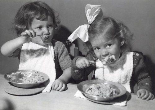 Eten en drinken.  Twee kleine meisjes eten met behulp van een lepel hun warme maaltijd dat in een metalen bordje wordt opgediend. Kinderbewaarplaats/crèche Marijke in Rotterdam 1950.