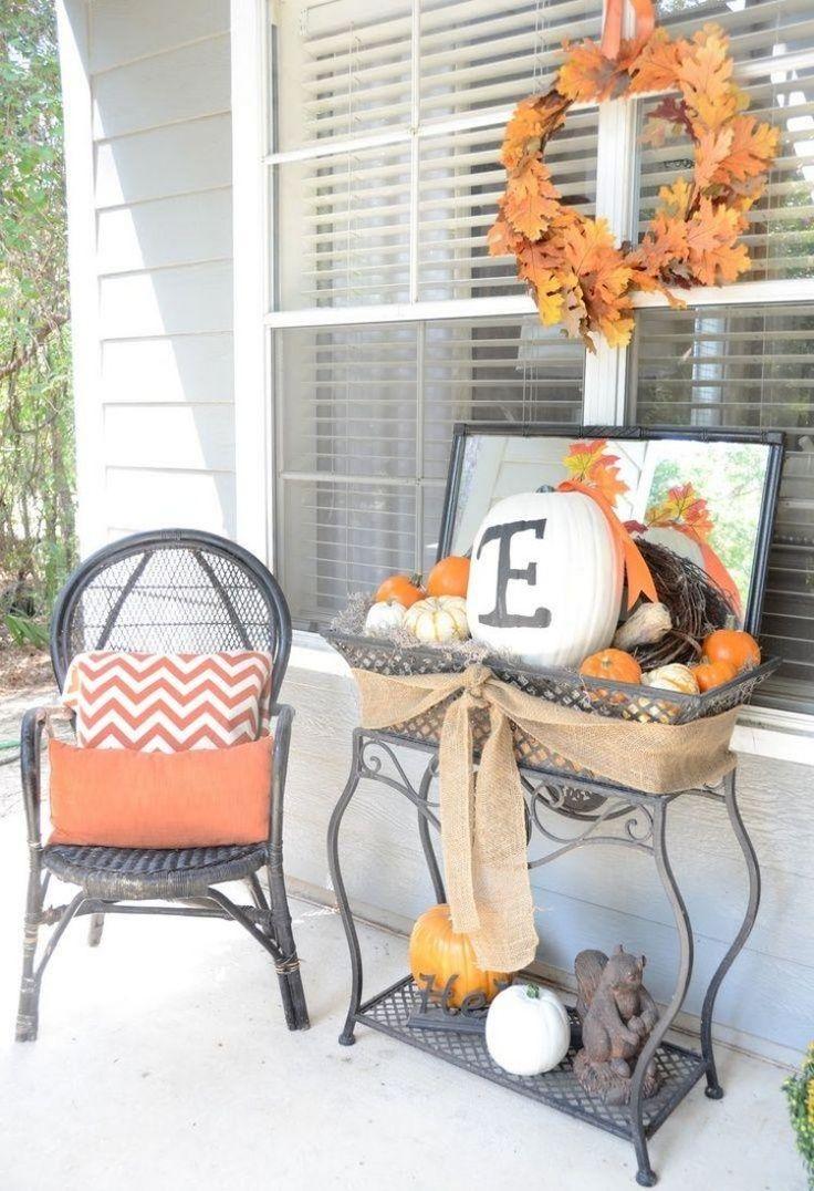 déco de terrasse en automne à partir de mini-citrouilles en blanc et orange, couronne de feuilles d'automne et ruban en toile de jute