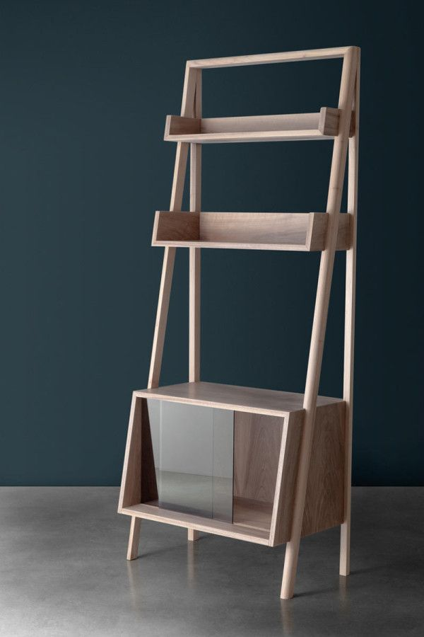 Libera is a freestanding, walnut bookshelf with a split support structure that holds a large storage box and two shelves.