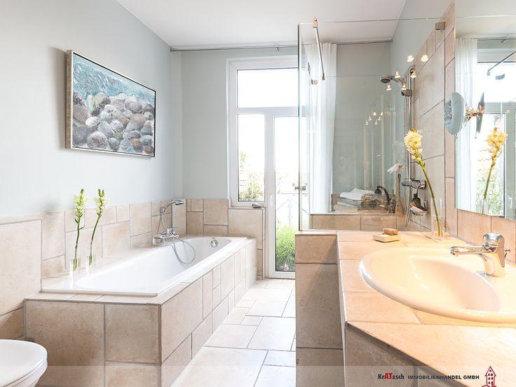 Der Landhausstil setzt sich im Badezimmer weiter fort. Ein bodentiefes Fensterelement gewährt auch von hier aus Zugang auf den Balkon und lässt unglaublich viel Licht in den Raum.  Die Sanitärobjekte wurde clever angeordnet und teilweise fest verbaut. Dadurch entstanden nützliche Ablageflächen. In dem knapp 8m² großem Raum fanden Badewanne, Dusche, Waschtisch, WC und Waschmaschine bequem Platz.