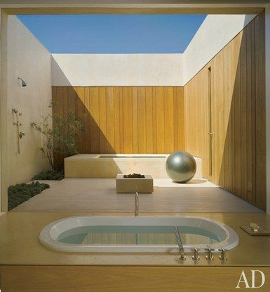 A Waterworks tub with Dornbracht fittings looks onto a courtyard featuring an outdoor shower, a hot tub, and a fire pit | archdigest.com